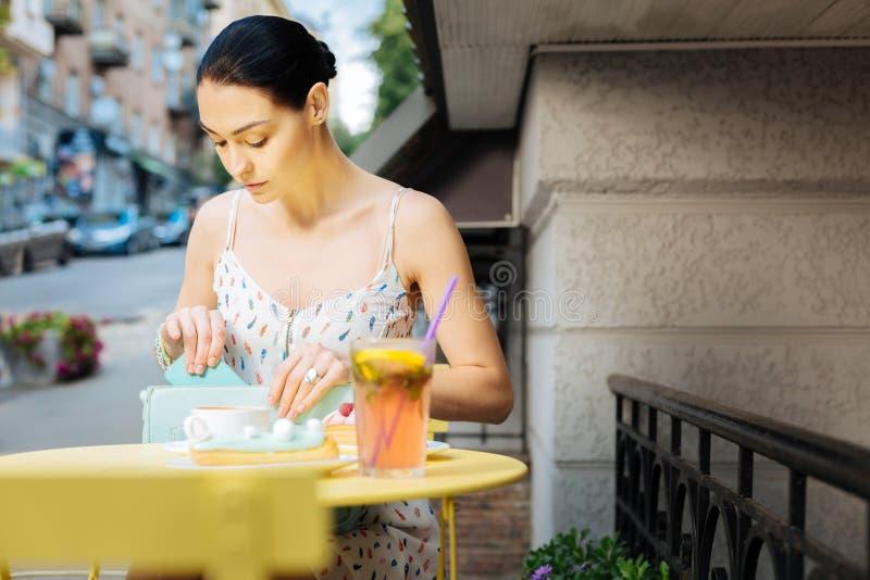 Mujer tranquila que se sienta en un café y que pone su smartphone en un bolso imagenes de archivo