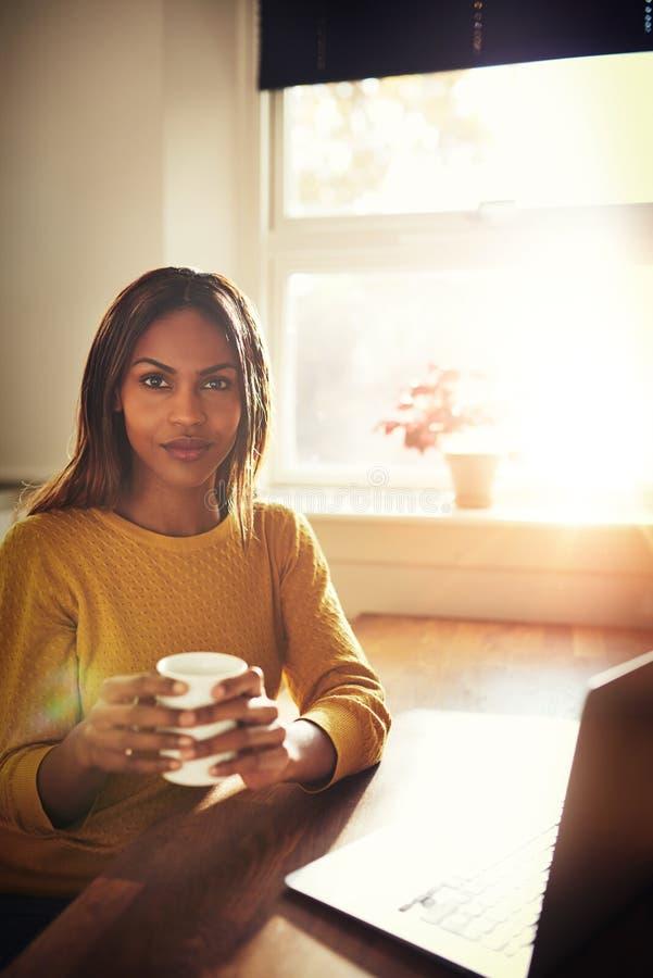 Mujer tranquila que sostiene el café cerca de ventana brillante fotografía de archivo