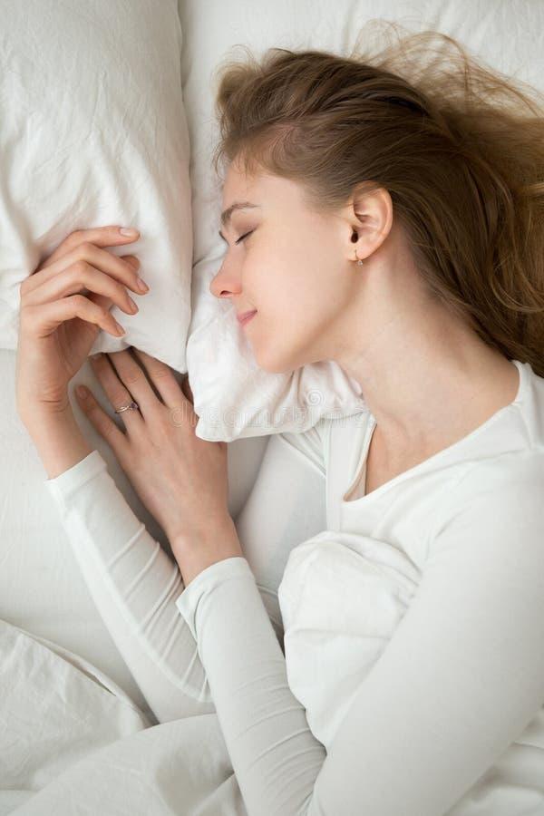 Mujer tranquila serena con los ojos cerrados que mienten en cama imagen de archivo