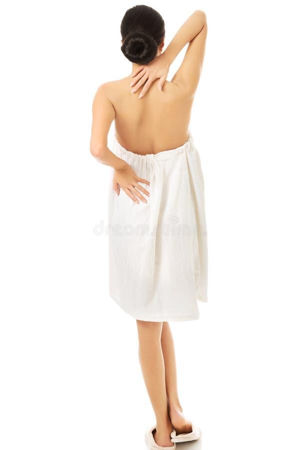 Mujer trasera de la visión envuelta en la toalla que la toca detrás fotos de archivo libres de regalías