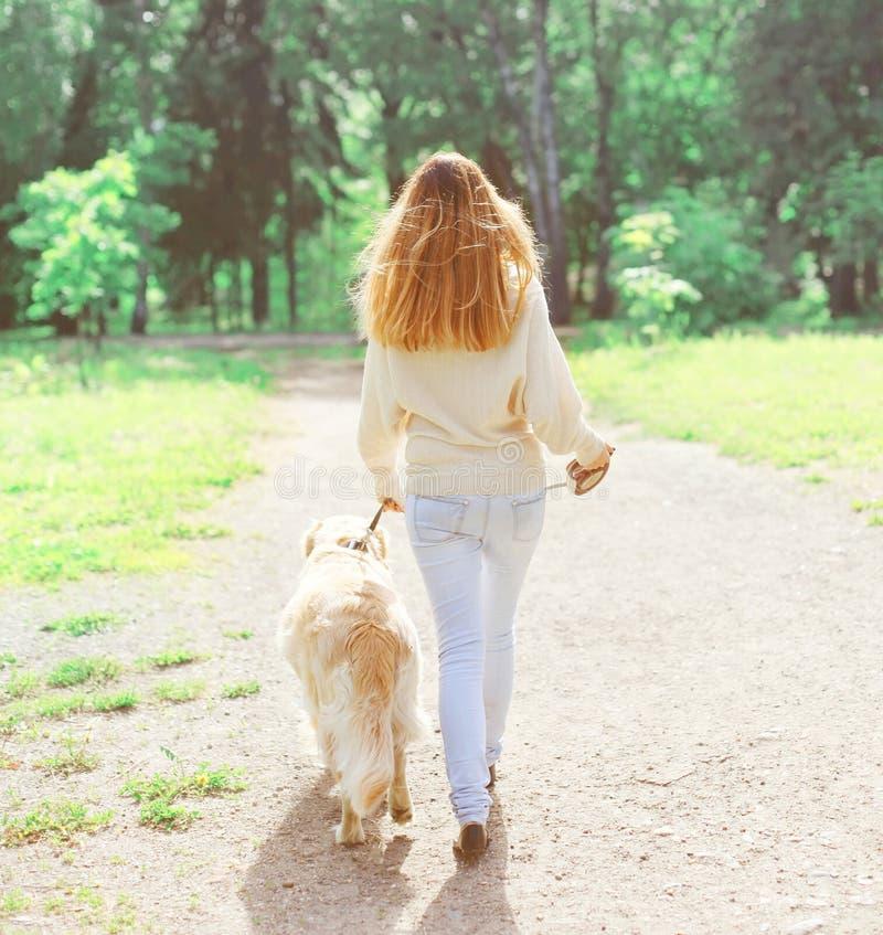 Mujer trasera del dueño de la visión y perro del golden retriever que camina en primavera fotografía de archivo