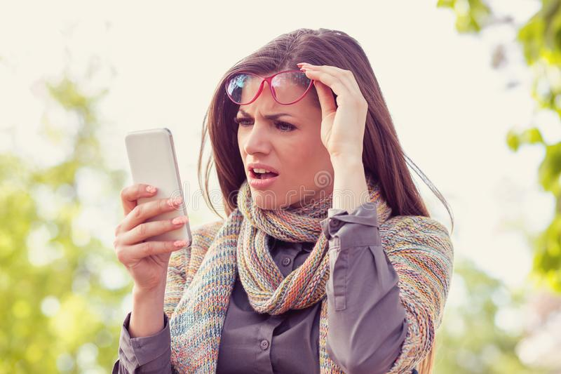 Mujer trastornada enfadada en los vidrios que miran su teléfono elegante con la frustración mientras que camina en una calle imagen de archivo libre de regalías