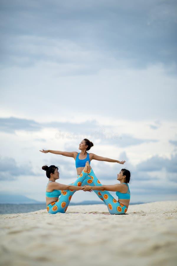 Mujer tres que juega actitud de la yoga en la playa de la arena imágenes de archivo libres de regalías