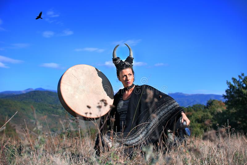Mujer tribal con los cuernos que juegan un tambor del búfalo en la montaña fotos de archivo libres de regalías