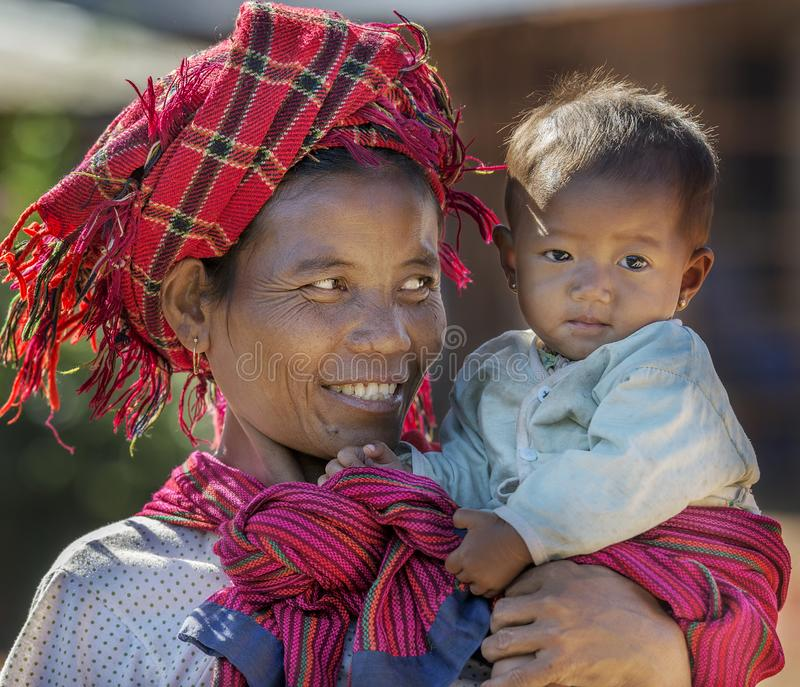 Mujer tribal de Intha que detiene a su niño en su brazo feliz, Inle Myanmar foto de archivo