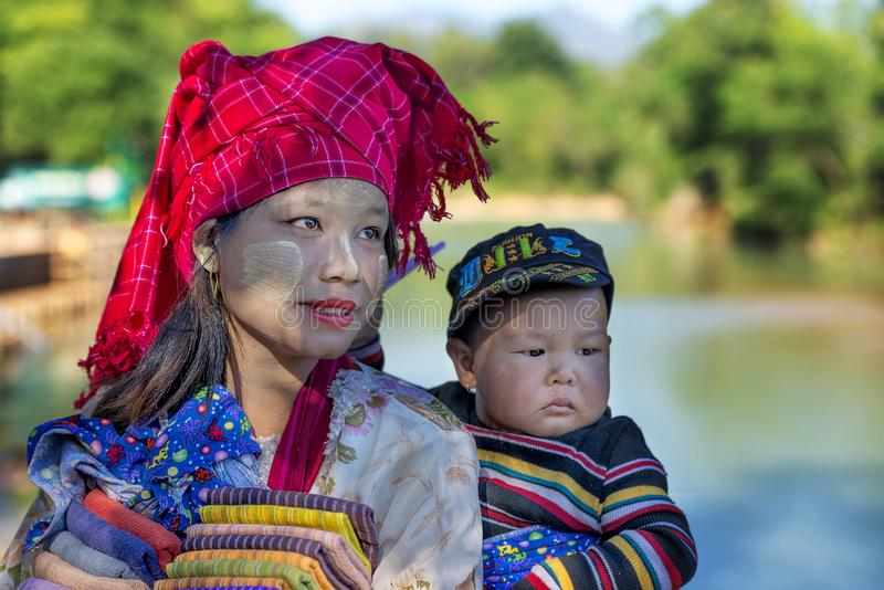 Mujer tribal de Intha que detiene a su niño en la parte posterior que vende los paños de seda en INle, Myanmar foto de archivo libre de regalías