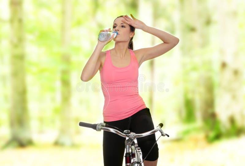 Mujer triguena atractiva con la bici imagen de archivo