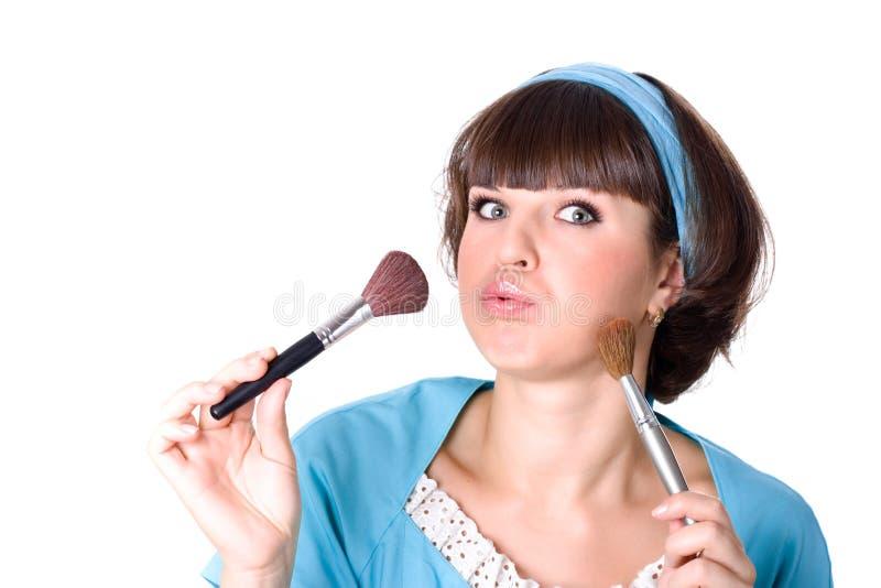 Mujer triguena con dos cepillos del maquillaje foto de archivo