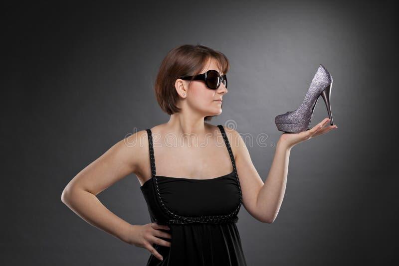 Mujer triguena con las gafas de sol que sostienen un zapato imagenes de archivo