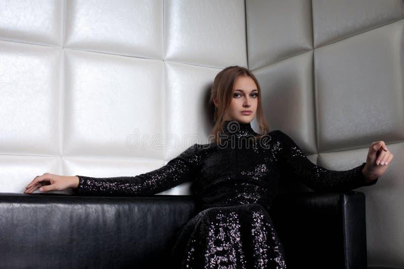 Mujer triguena de la belleza en el sofá en club nocturno fotografía de archivo libre de regalías