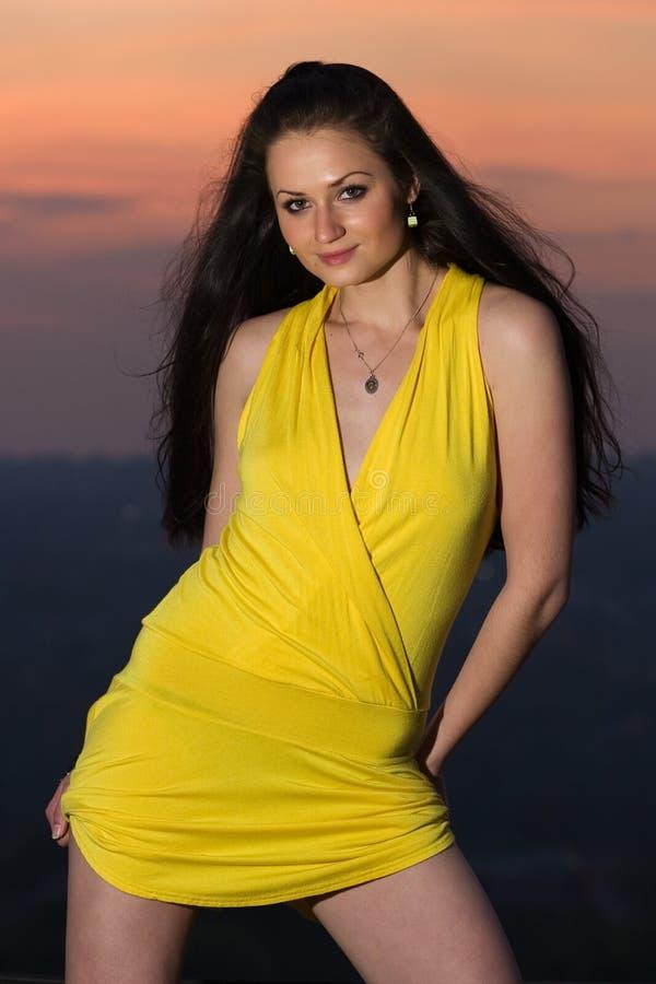 Mujer triguena joven atractiva en alineada amarilla corta fotografía de archivo