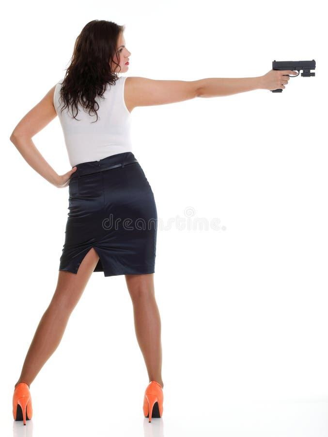 Mujer triguena joven con el arma aislado en blanco imagen de archivo libre de regalías
