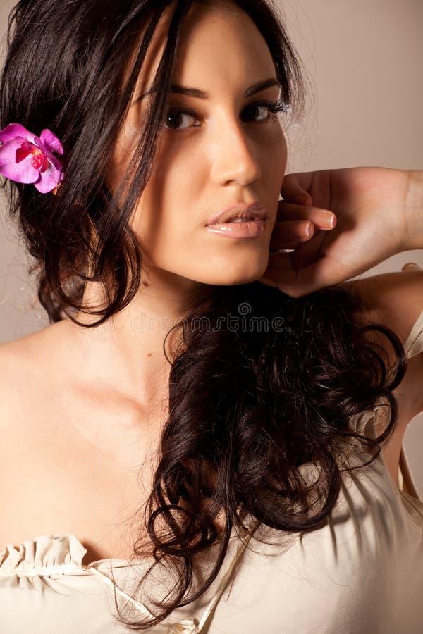 Mujer triguena joven con la flor en pelo rizado imagen de archivo libre de regalías