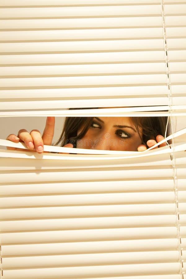 Mujer triguena joven que mira a través de las persianas fotografía de archivo libre de regalías
