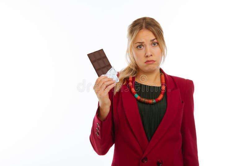 Mujer triste agradable que sostiene una barra del chocolate fotografía de archivo