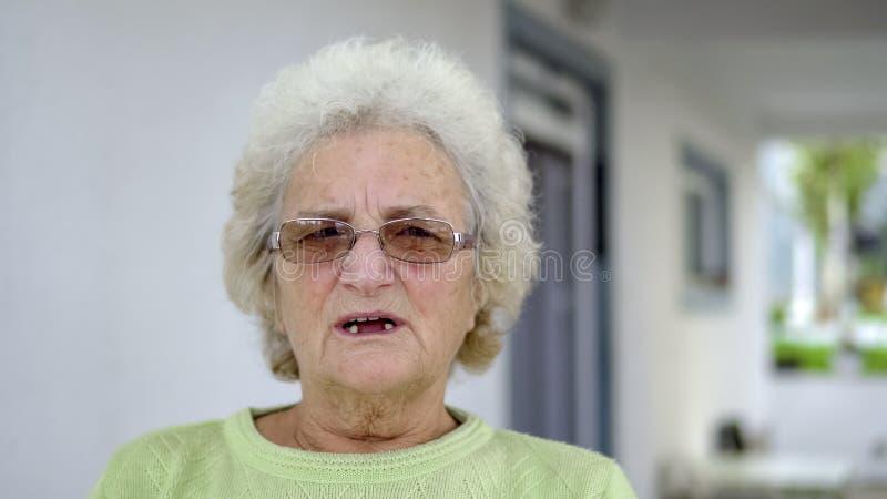 mujer triste blanca mayor que se sienta y que piensa al aire libre imagenes de archivo
