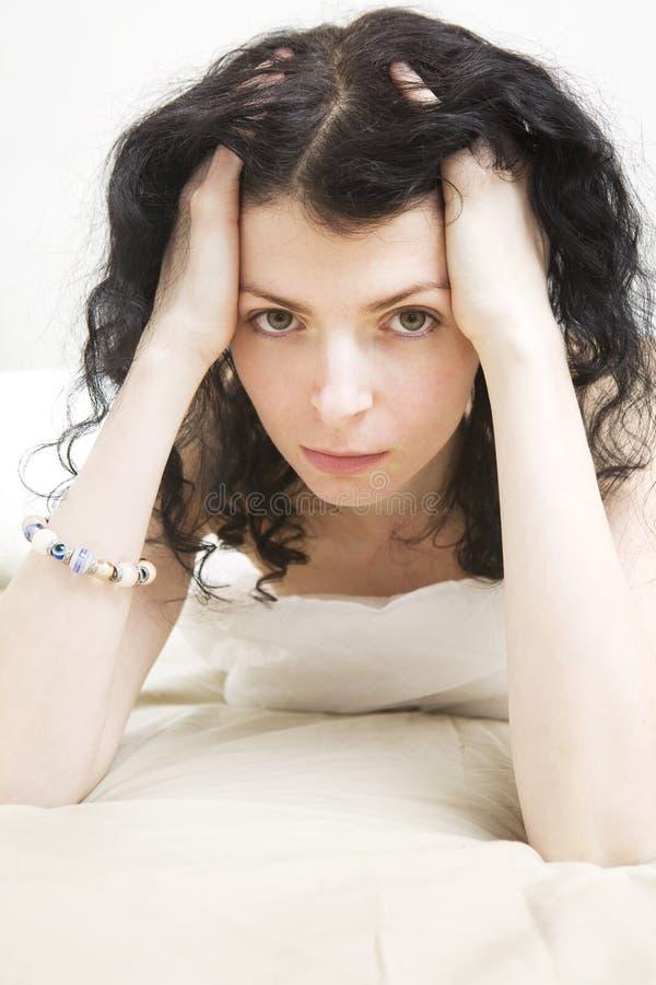 Mujer triste con el pelo del enrollamiento foto de archivo