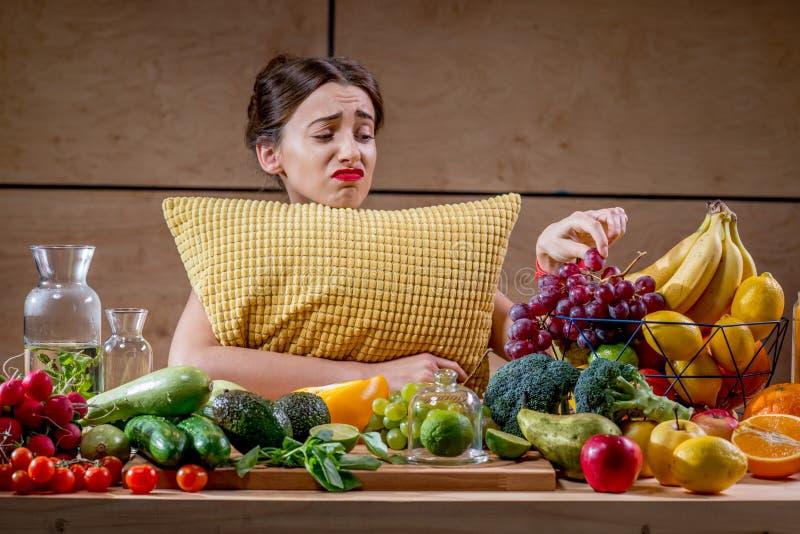 Mujer triste con la almohada que mira en la comida imágenes de archivo libres de regalías