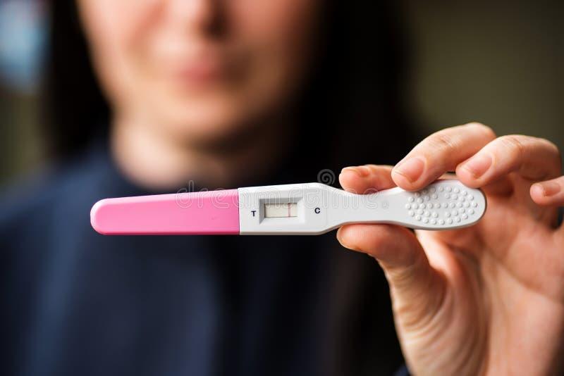 Mujer triste con la prueba de embarazo casera imagen de archivo libre de regalías