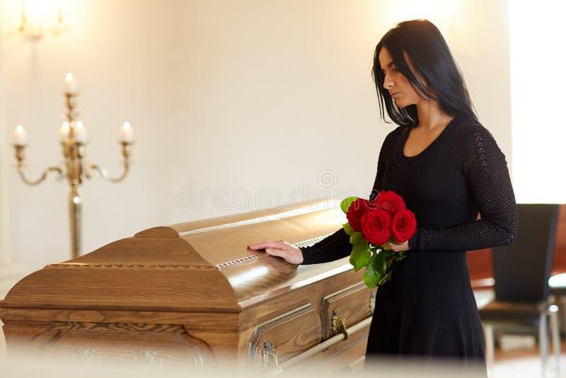 Mujer triste con la rosa y el ataúd del rojo en el entierro fotos de archivo