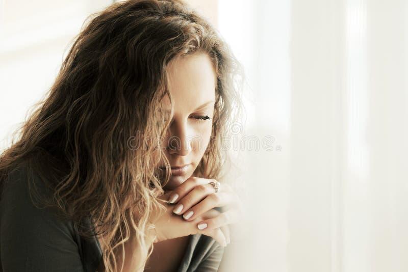 Mujer triste con los pelos rizados largos que miran abajo imagen de archivo libre de regalías