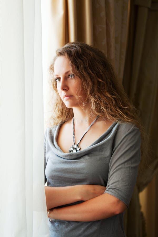 Mujer triste contra una ventana. fotografía de archivo libre de regalías