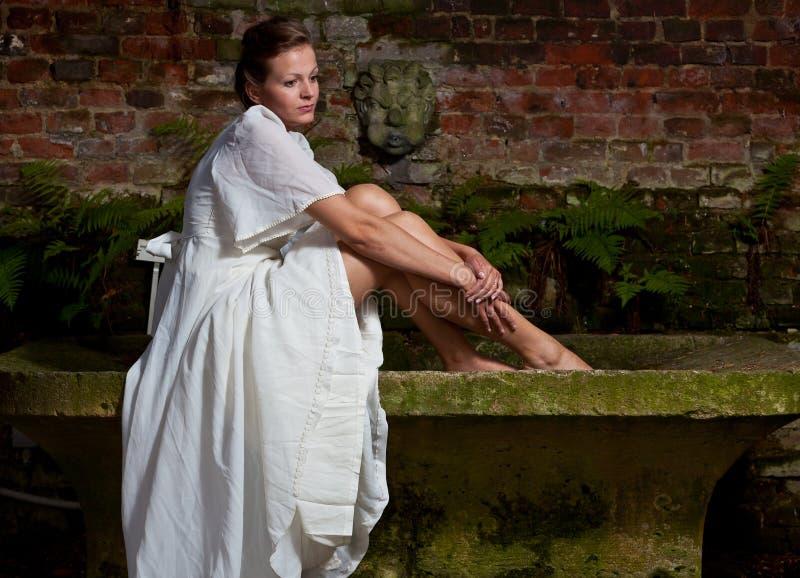 Mujer triste en el vestido blanco que se sienta en un banco de piedra imagenes de archivo