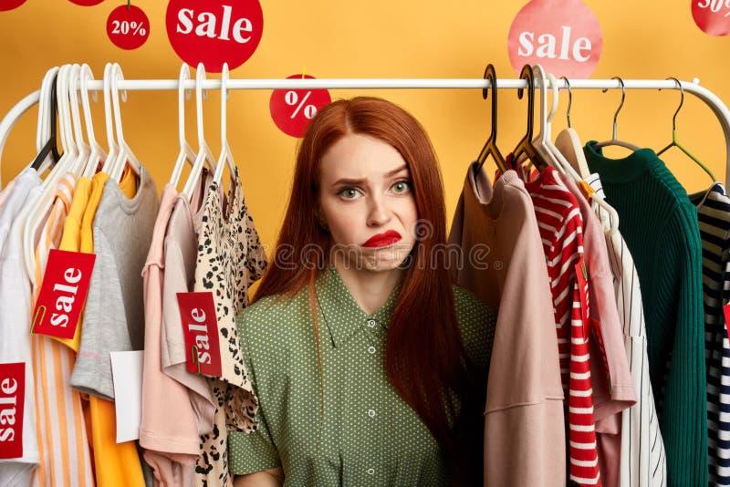 Mujer triste enojada infeliz joven que elige la ropa en el estante fotos de archivo libres de regalías