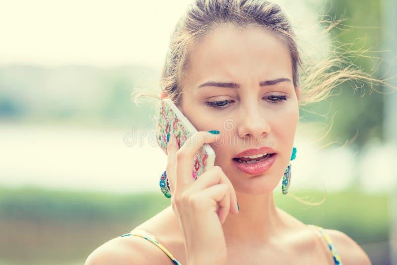 Mujer triste, escéptica trastornada que habla en el teléfono fotografía de archivo