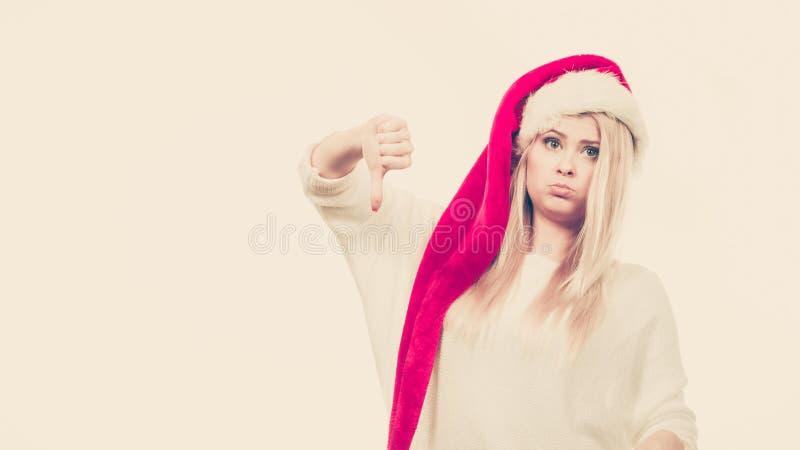 Mujer triste infeliz que lleva el sombrero del ayudante de Santa Claus imagen de archivo libre de regalías