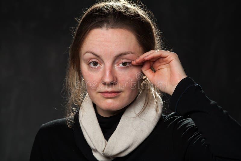 Mujer triste joven, limpiando los rasgones imagen de archivo libre de regalías