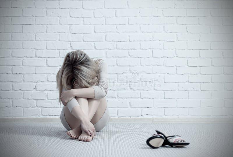 Mujer triste joven que se sienta en el piso y el griterío fotos de archivo