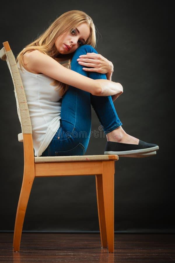 Mujer triste joven que se sienta en silla fotografía de archivo
