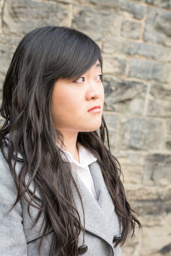 Mujer triste por una pared de piedra imagen de archivo