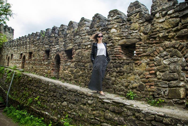 Mujer triste que camina en la pared de la fortaleza foto de archivo