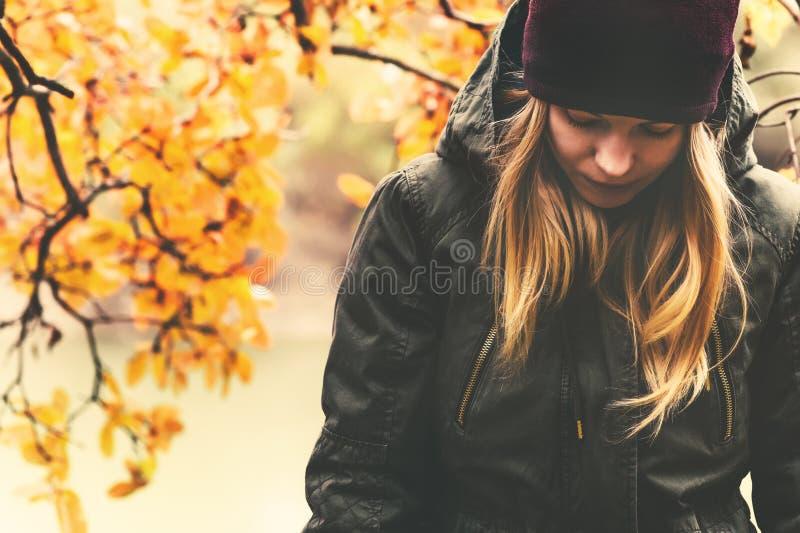 Mujer triste que camina en melancolía estacional del parque imagen de archivo
