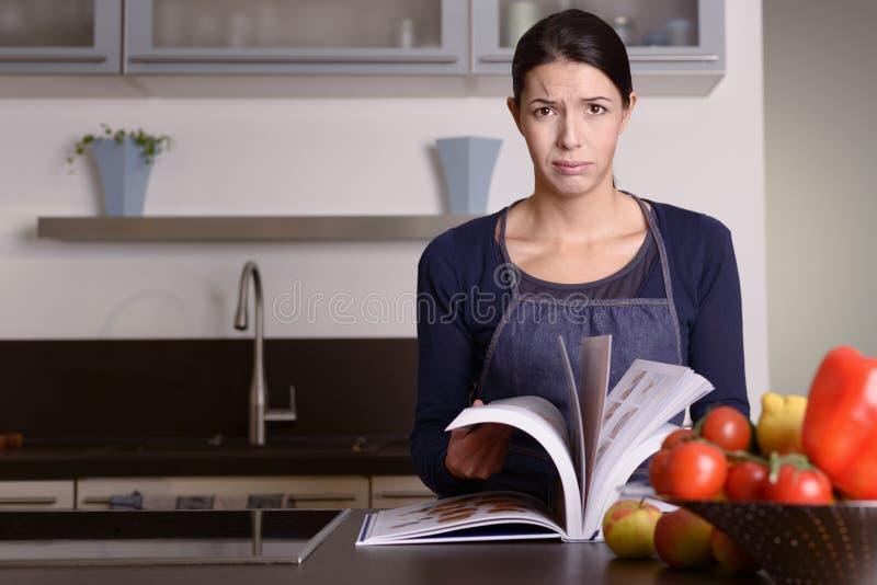 Mujer triste que celebra el libro de la receta en la cocina fotos de archivo