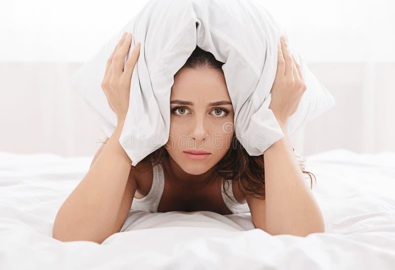 Mujer triste que miente en cama matrimonial y que mira en el sitio vacío imágenes de archivo libres de regalías