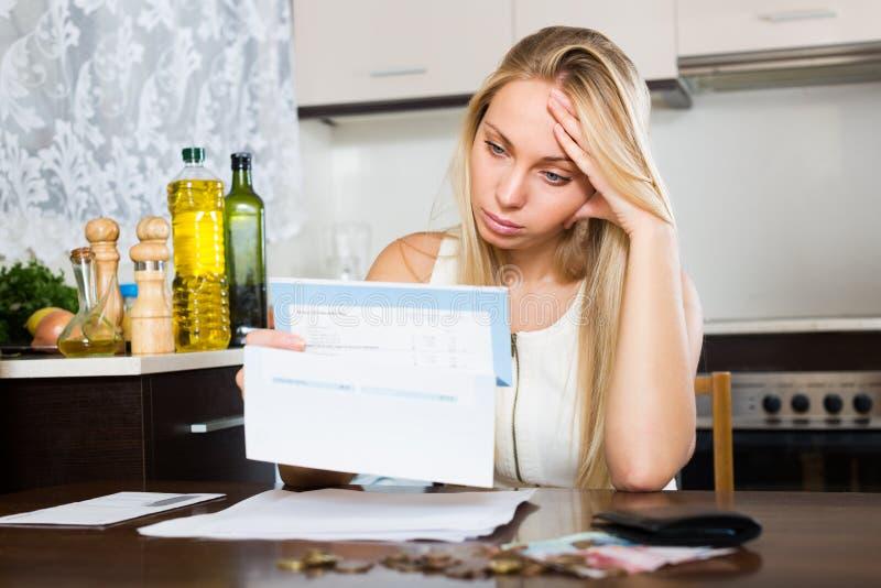 Mujer triste que piensa en problemas financieros imagen de archivo