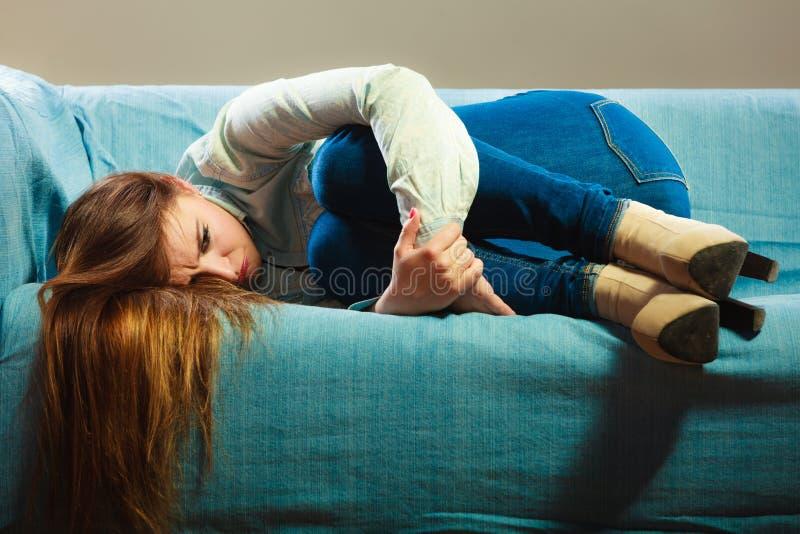 Mujer triste que pone en el sofá fotos de archivo libres de regalías