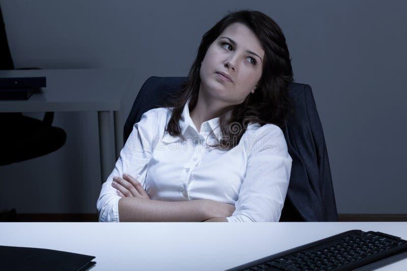 Mujer triste que se sienta en el escritorio fotografía de archivo