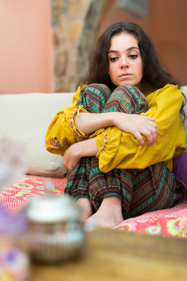 Mujer triste que se sienta en el sofá imágenes de archivo libres de regalías