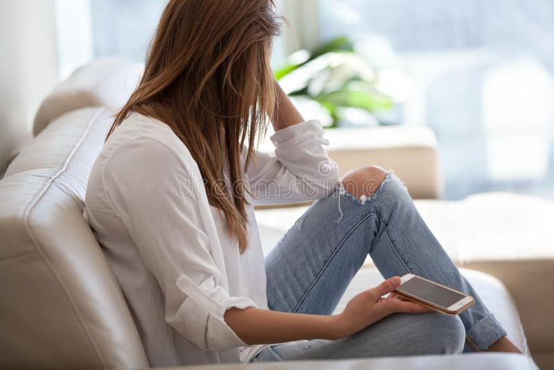 Mujer triste que se sienta en el sofá que lleva a cabo llamada que espera del teléfono para imagen de archivo