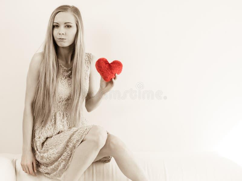 Mujer triste que sostiene la almohada roja en forma del coraz?n imagen de archivo libre de regalías