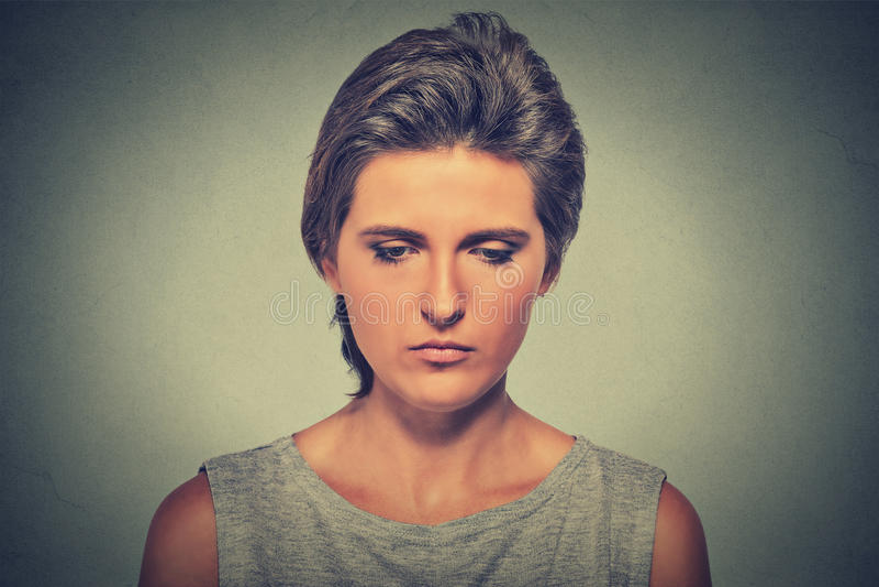 Mujer triste sola profundamente en los pensamientos que miran abajo imagenes de archivo