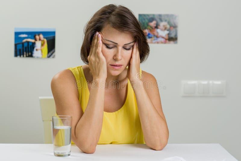 Mujer triste subrayada Ella lleva a cabo su cabeza en sus manos foto de archivo