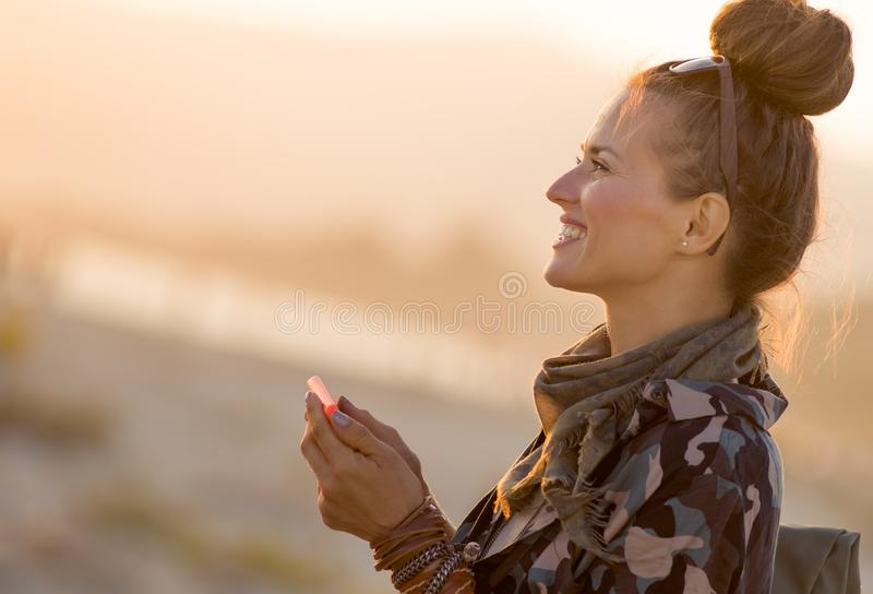Mujer turística apta sonriente con smartphone usando el app foto de archivo
