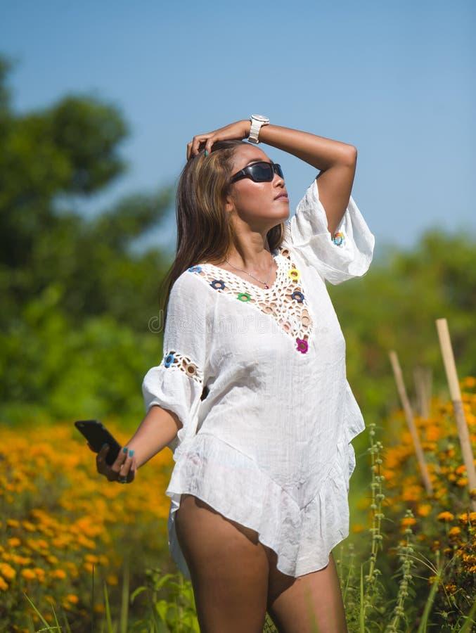 Mujer turística asiática joven feliz y hermosa que toma imagen del selfie en paisaje natural anaranjado magnífico del campo de fl imágenes de archivo libres de regalías