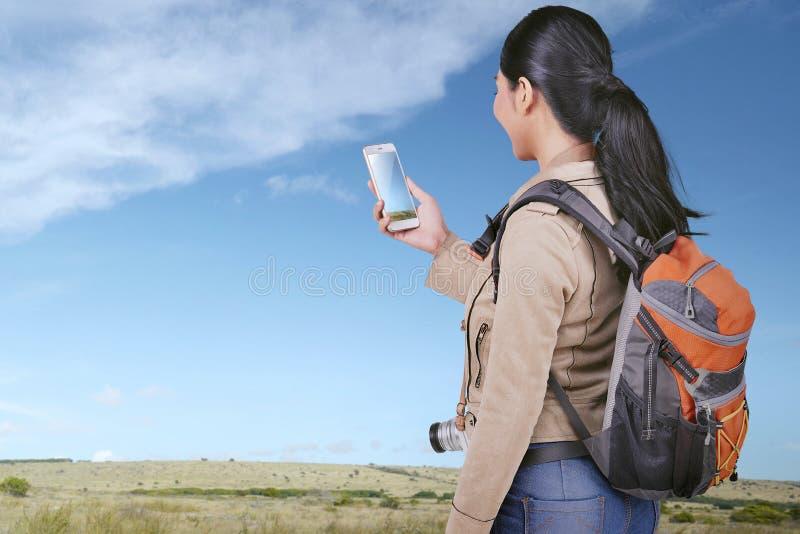 Mujer turística asiática joven que mira las fotos en su teléfono elegante imagen de archivo