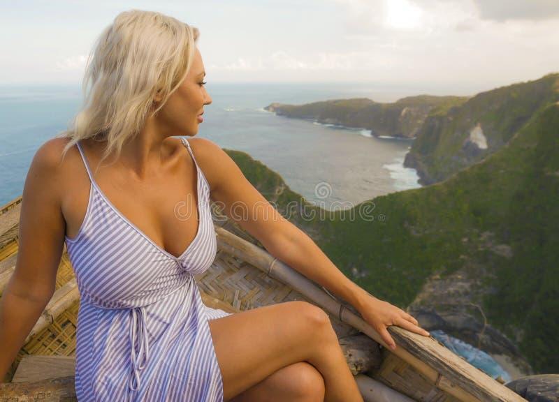 Mujer turística atractiva y feliz joven que considera la vista imponente de la playa hermosa del acantilado del mar el goce del p fotos de archivo